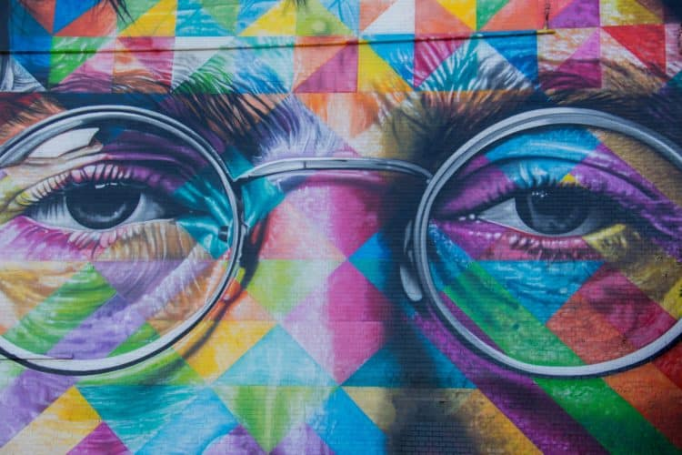 Colorful mural of the eyes and glasses of John Lennon of the Beatles on a brick wall in the United Kingdom