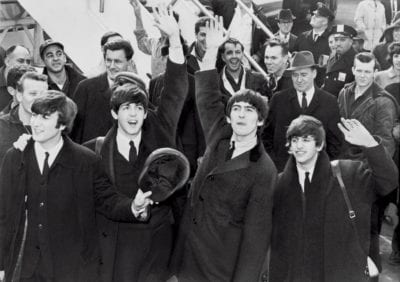 Black and white photo of the Beatles rock band in a crowd waving to fans