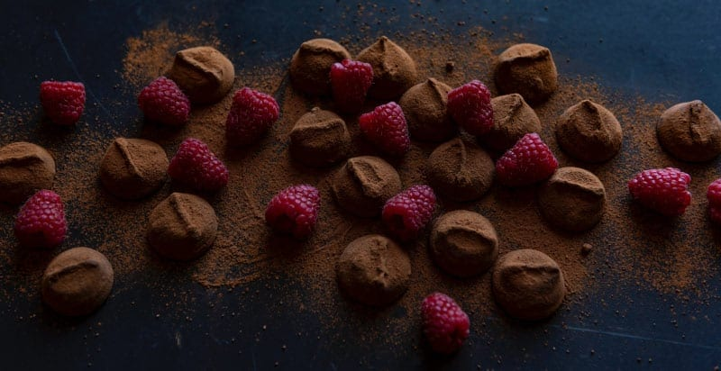 Aerial view of a cluster of chocolates intermixed with raspberries, dusted with powdered chocolate