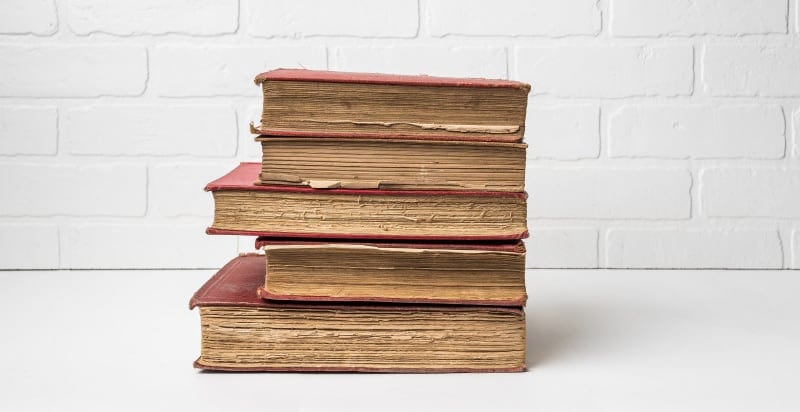A stack of 5 old books with brown pages and red covers against a white brick wall