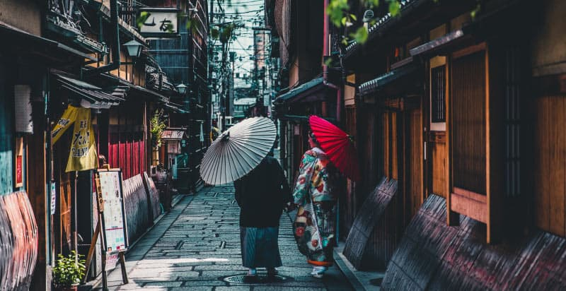 Two Japanese women, on wearing a colorful kimono, hold parasols while walking down a street in Kyoto, Japan