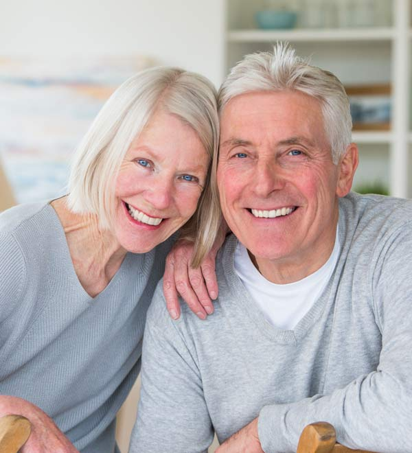 Older couple smiling and showing healthy teeth thanks to restorative dental care.