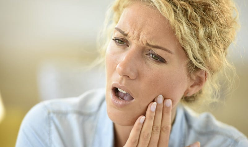 Blonde woman cringes and touches her cheek due to extreme tooth pain from dry socket