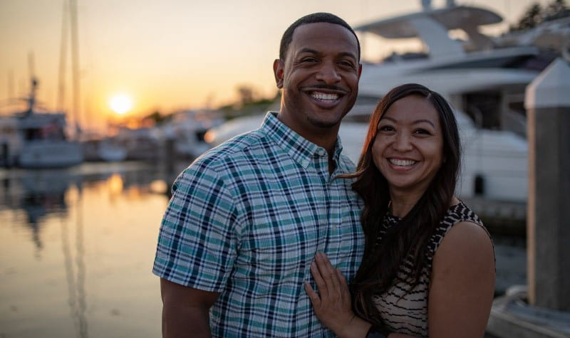 Dark-haired couple stands close together as they smile by a boat while standing on a pier as the sun sets