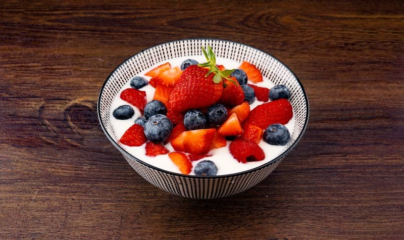 Aerial view of a bowl filled with white yogurt and fresh strawberries and blueberries on a wooden counter