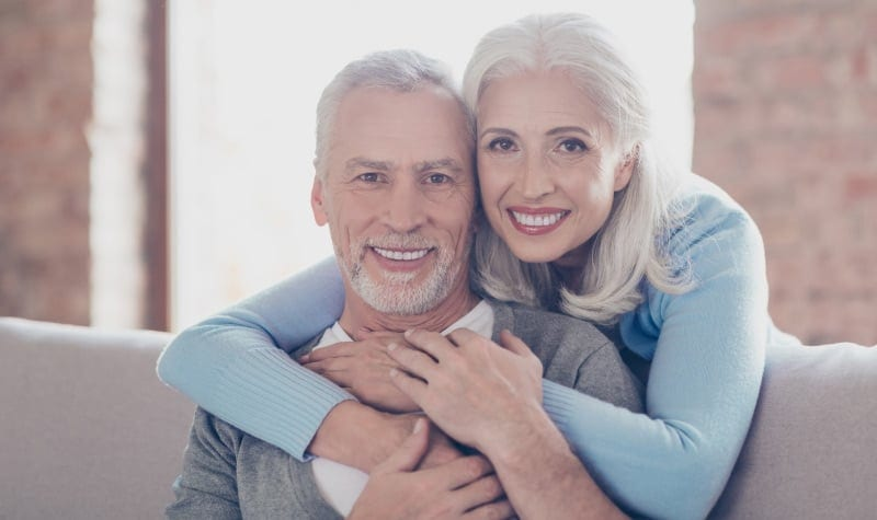 A white-haired senior couple wearing dentures smiles as they embrace